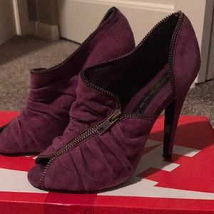 Purple suede heels with a zipper detail.
